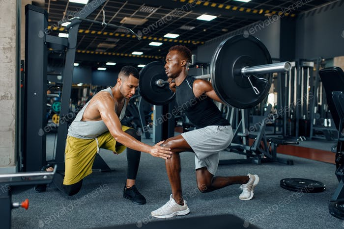 Muscular sportsman and trainer on training in gym
