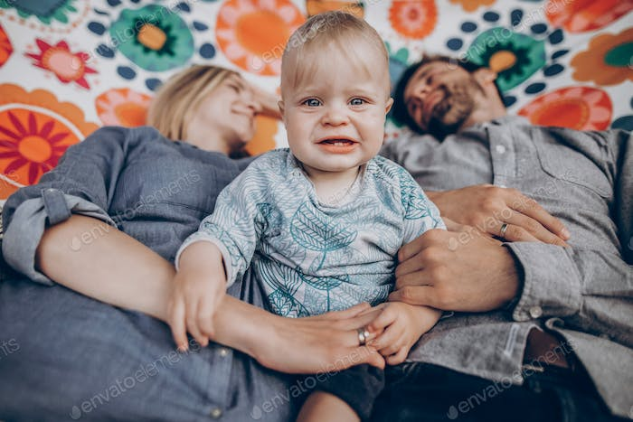 Cute family resting on boho hammock with smiling baby boy