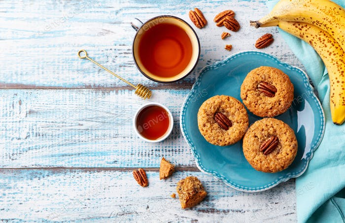 Pecan Nut, Banana Muffins on a Plate with Cup of Tea. Blue Wooden Background. Top View. Copy Space.