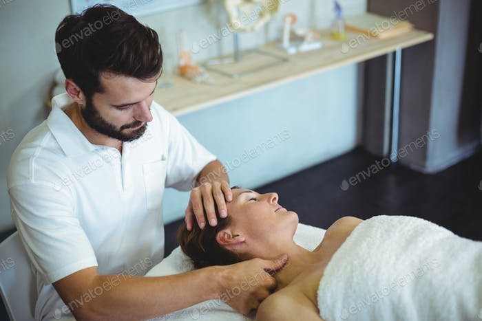 Portrait of smiling physiotherapist sitting with spine model