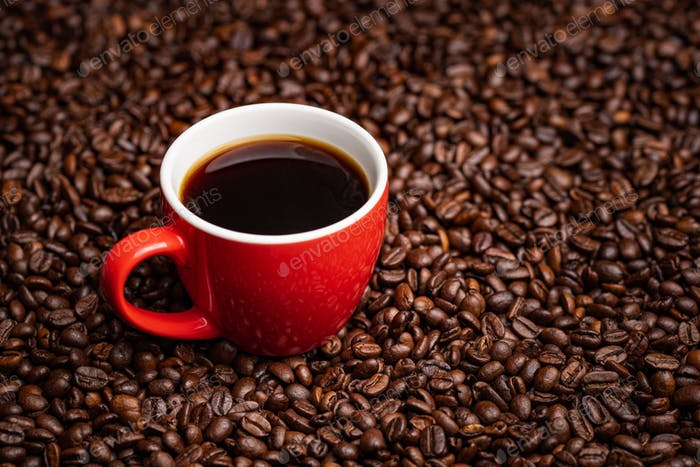 Red Cup of black coffee on table covered with coffee beans