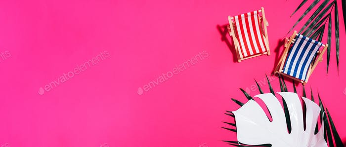 Deck chairs with hard shadow, monstera and palm leaves on pink paper background. Flat lay and copy