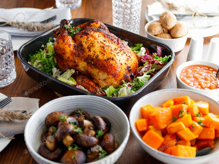 Decorated festive table with whole roasted chicken, salad, pumpkin, beans and walnut