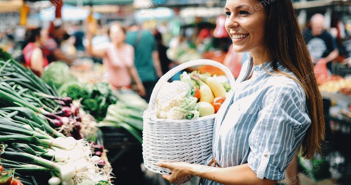 Picture of woman at marketplace buying vegetables