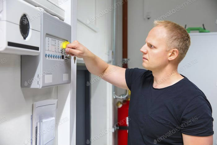 IT Technician Opening Fire Panel In Server Room