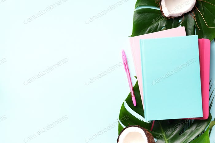 Green monstera, palm leaves, coconut, notebooks over pink background. Female blog writer workspace