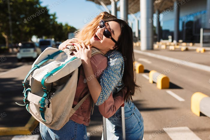 Cheerful girl in sunglasses happily hugging her female friend wi