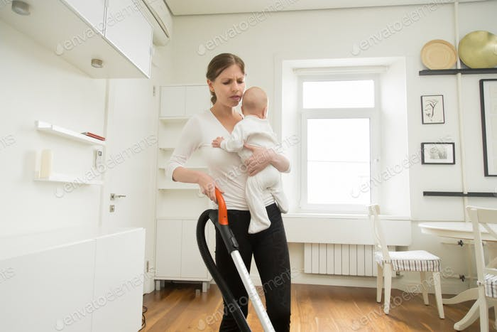 Frustrated woman cleaning the carpet holding a newborn