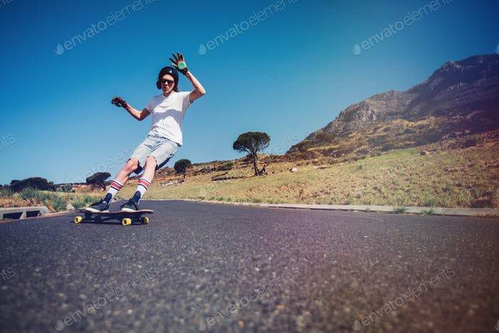 Young man longboarding on a road