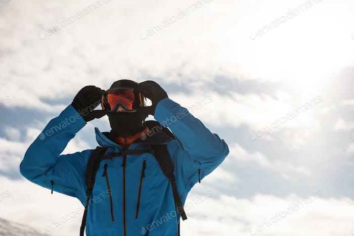 Skier adjusting his sunglasses
