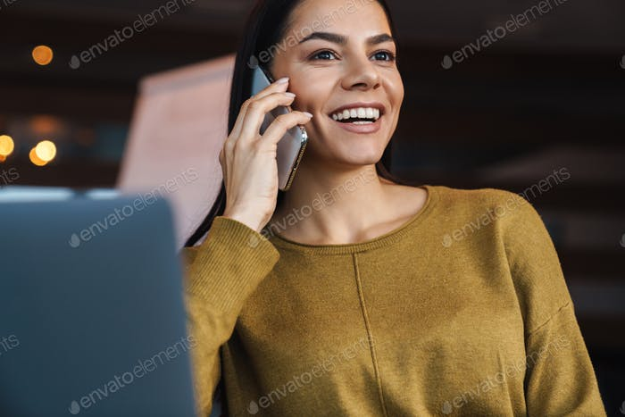 Image of businesswoman talking on cellphone and using laptop in office