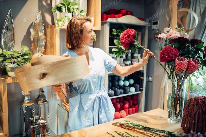Florist schmückt Komposition mit Birkenrinde