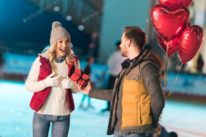 young man holding heart shaped balloons and presenting gift box to excited girlfriend on rink