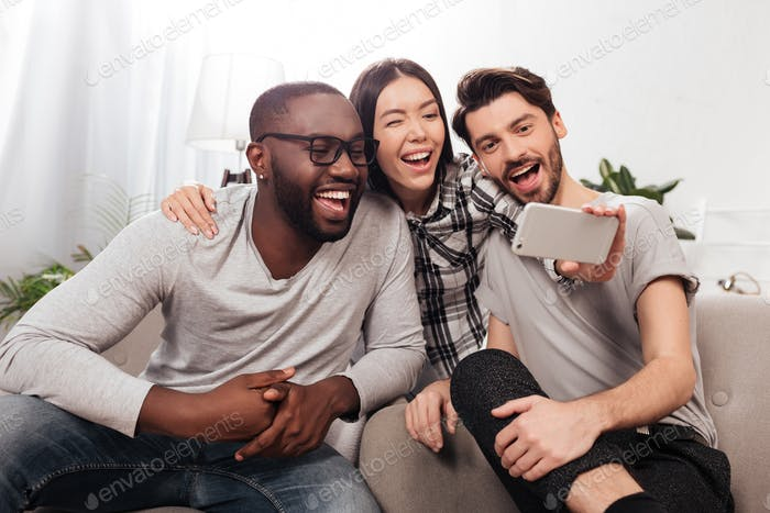 Group of young friends sitting on sofa at home and taking selfie while spending time together