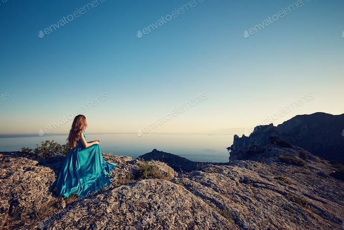 Young beautiful woman in blue dress looking to mountains sea