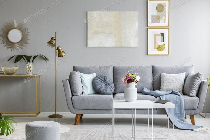 Gold mirror above shelf with plant in grey living room interior