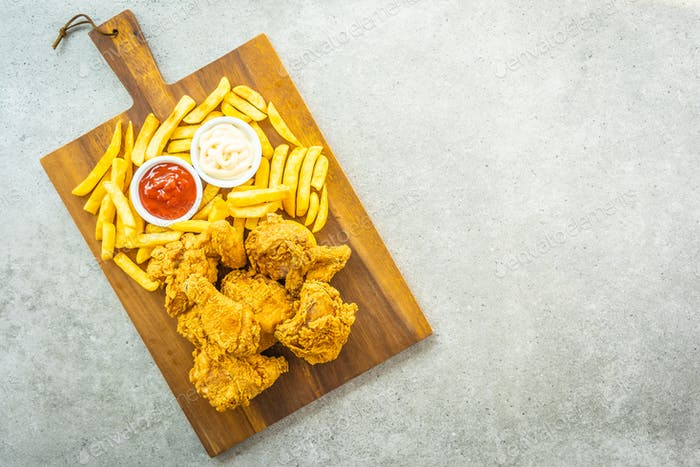 Fried chicken wings with french fries and tomato or ketchup and