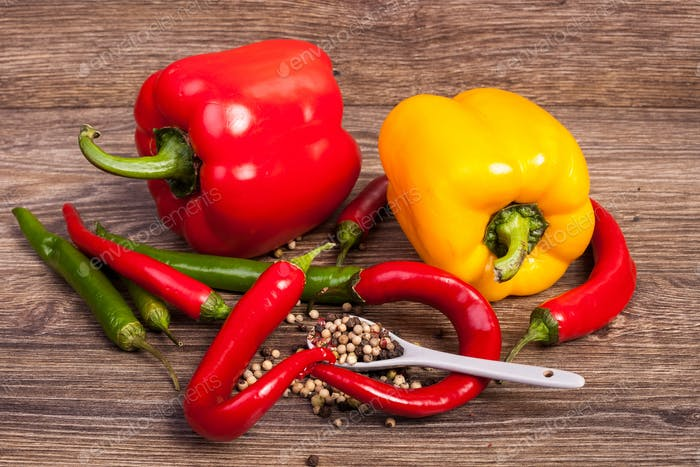 Sweet and spicy peppers on wooden background