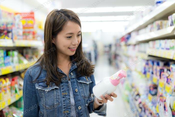 Женщина покупает уход за человеком в продуктовом магазине