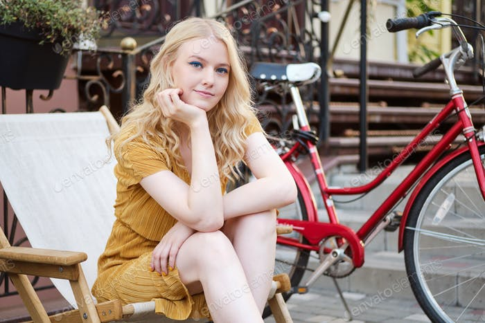 Attractive blond girl in dress lovely looking in camera resting with classic bicycle on city street