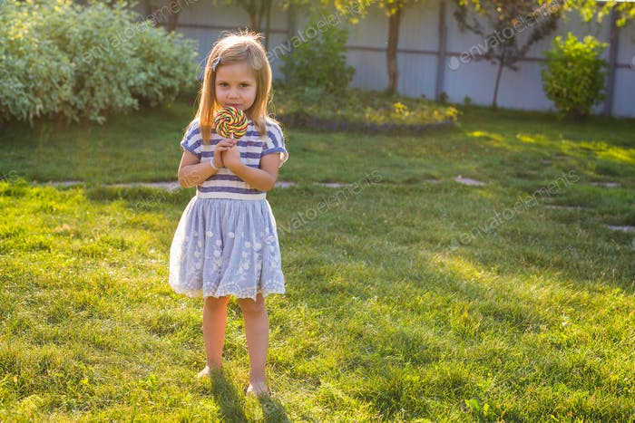 cute little girl eating a lollipop on the grass in summertime.