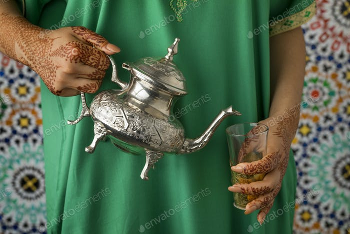 Moroccan woman with henna painted hands pouring tea