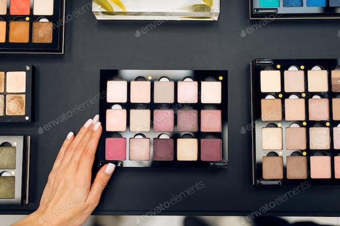 Woman with brush choosing shadows, cosmetics store