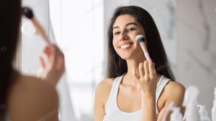 Girl Applying Face Powder Using Makeup Brush Standing In Bathroom