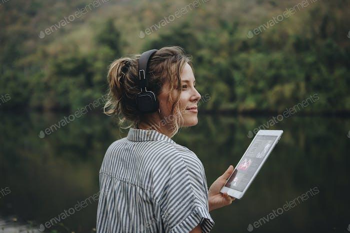 Frau allein in der Natur Musik hören mit Kopfhörern