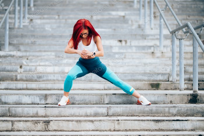 Portrait of caucasian female in sportswear exercising outdoors on stairs