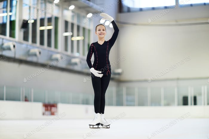Little Figure Skater Posing in Rink