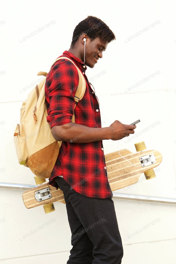 handsome young african man with skateboard and back pack looking at cell phone