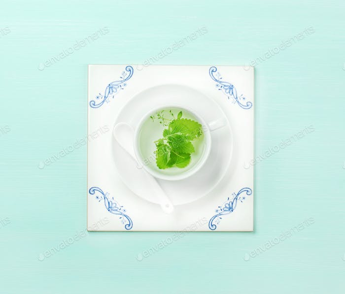 Cup of tea on white tile board over mint background