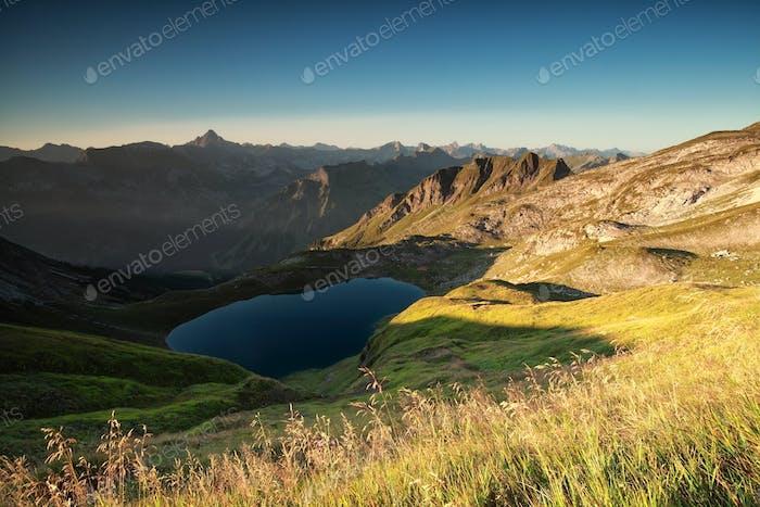 sunrise over alpine peaks and lake