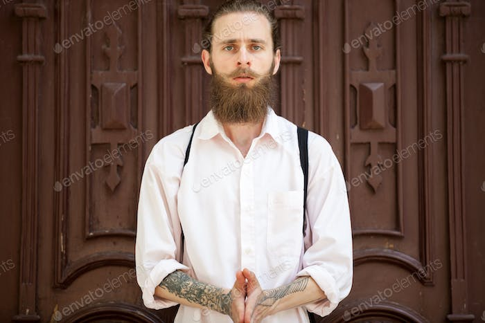 Portrait of bearded hipster in front of a door