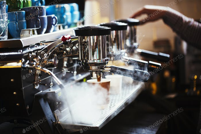 Specialist coffee shop. A person working at a large coffee machine, with three perculating