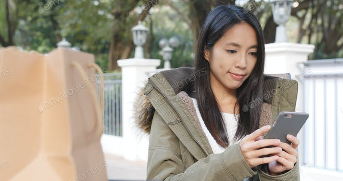 Woman using smart phone at outdoor coffee shop