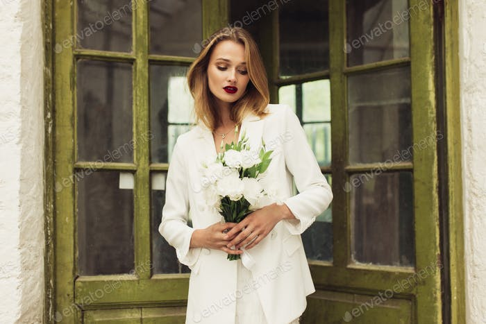 Young beautiful woman in white jacket and dress holding little b