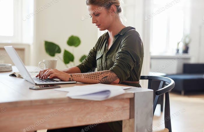 Businesswoman working on laptop at home office