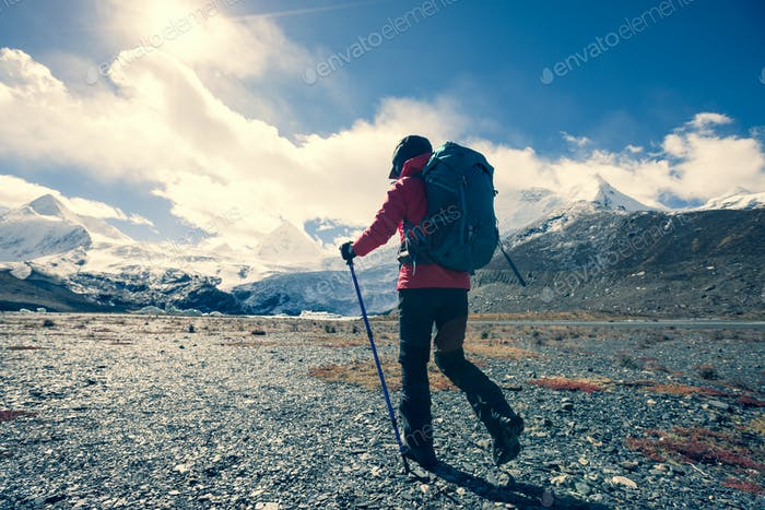 Woman hiker with camera in winter high altitude mountains