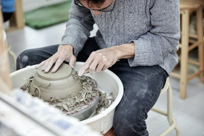 A man using a pottery wheel, shaping a pot base with a small handheld tool shaving off excess clay.
