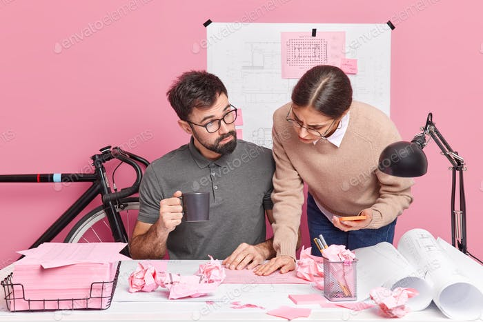 Two graphic designers collaborate on building sketches share different ideas for creating new room b
