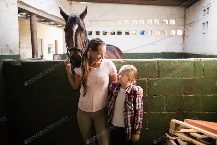 Sisters talking while standing by horse