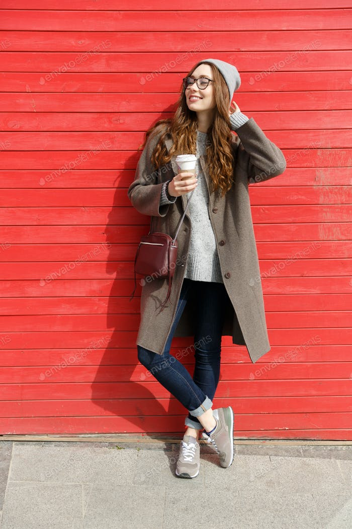 Smiling relaxed young woman standing and drinking take away coffee