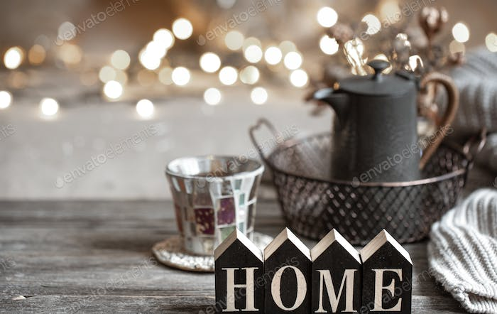 Cozy background with the wooden word home on a blurred background with lights.