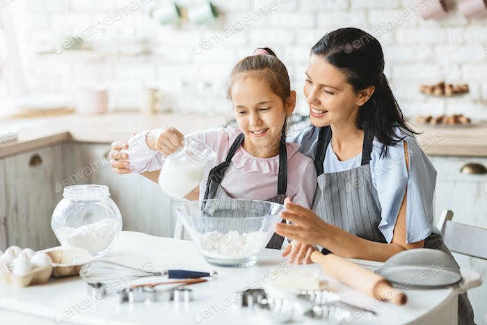 Smiling Family Of Mother And Daughter Cooking Tasty Biscuit Together