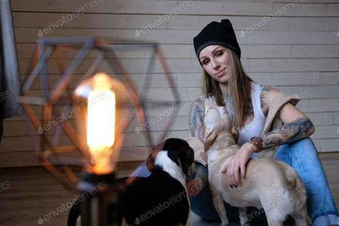 Portrait of a hipster tattoed girl playing with her little dogs while sitting on a wooden floor.
