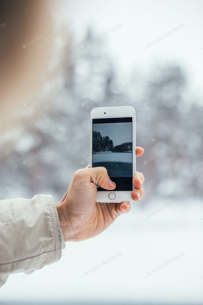 Man makes photo of snow winter on smartphone