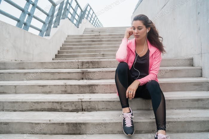 Athletic woman listening to music on a break from training.
