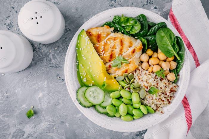 Buddha Schüssel mit Spinat, Quinoa, Kichererbsen, Huhn, Avocado, Edamame Bohnen, Gurken, Sesam.
